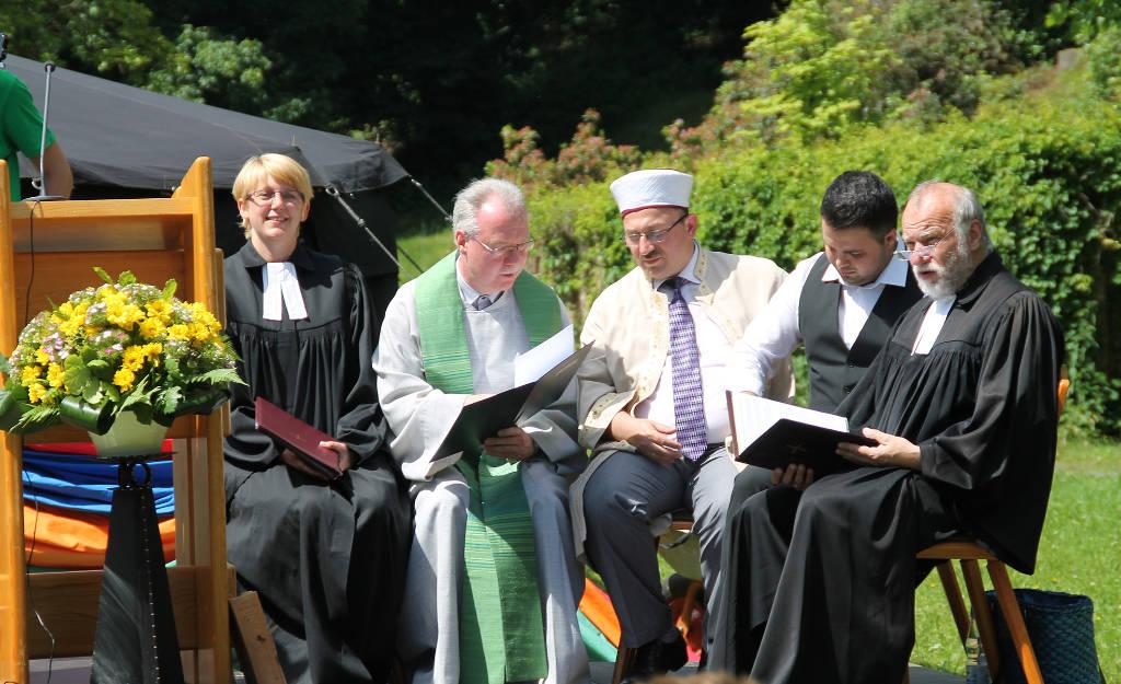 Die Pfarrer der ev. und kath. Kirchengemeinden mit dem Imam der muslimischen Gemeinde auf einer Bühne